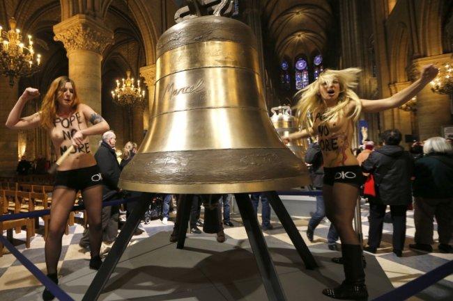 Les connes gouines de FEMEN frappant hystériquement sur une des cloches de notre-dame exposées dans la cathédrale avant leur installation dans le clocher.