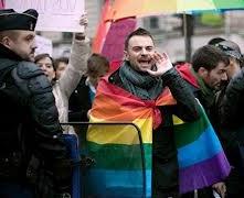 homosexuel drapé d'un drapeau gay protégé par la police